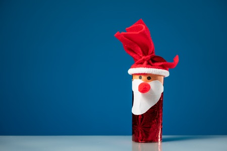 A figure of Santa Claus made of a toilet paper roll by a child on blue background