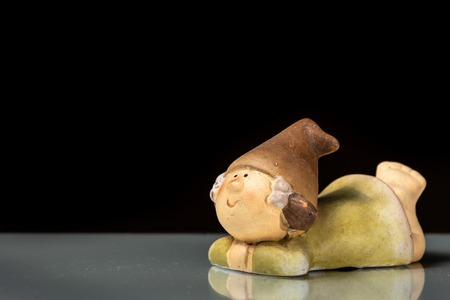 A small figurine of a gnome lying on a reflective surface isolated on black background 免版税图像