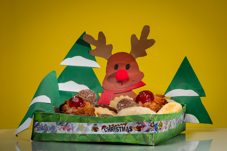 A small bowl made of paper with various christmas cookies, trees and reindeer Stock Photo