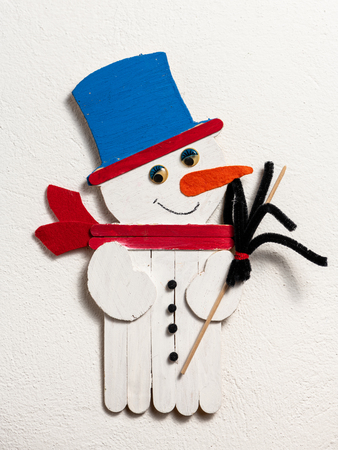 Figure of a funny snowman made of wood by a child on white background
