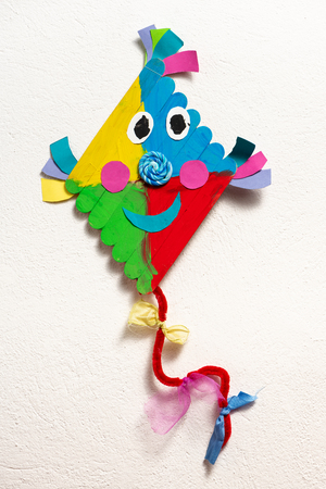 A colorful kite made of wood by a child on white background