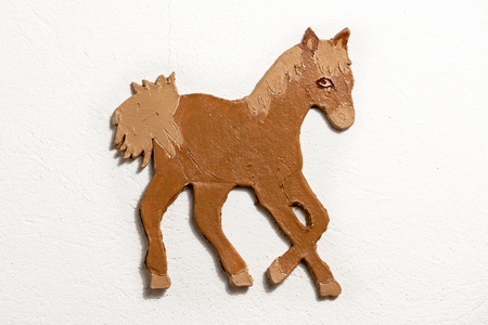 Brown figure of a horse made of clay by a child on white background