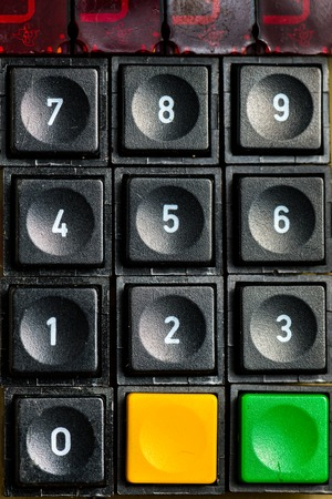 An old numeric keypad with additional buttons (black, yellow, green), lying on a wooden tabel