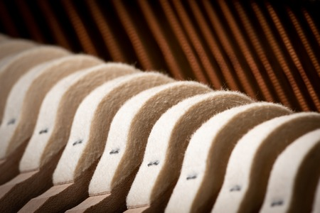 Abstract closeup of the interior of an upright piano, hammer and strings