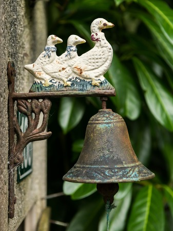 Old vintage rusty doorbell with three ducks, made of iron
