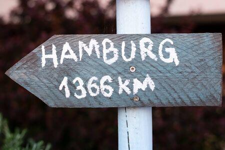 graues Schild mit weißer Schrift auf einem weißen Mast, der nach Hamburg weist Standard-Bild