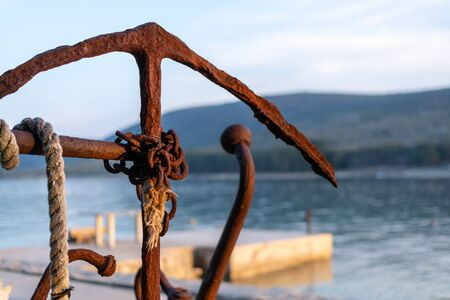 rusty old anchor with rope and chain in the evening sun by the sea