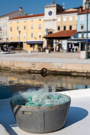 a bucket full of fishing nets standing in a port in Cres (Croatia)