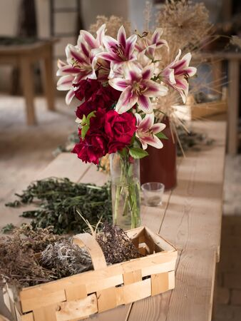 Various flowers (lilies) in a vase standing on a wooden table