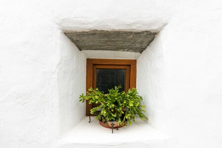 Flowers in front of a small window of a very old house in Glurns (South Tyrol, Italy) Stock fotó