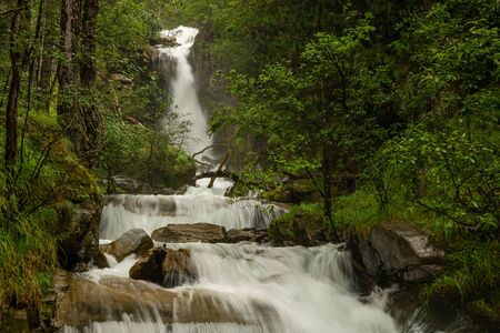 Waterfall in the forest near Schlanders (South Tyrol, Italy) on a cloudy day in summer