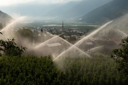 Water sprinklers in front of Schlanders (South Tyrol, Italy) on a cloudy day in summer Stock fotó