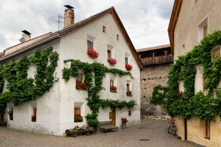 A very old white house with red flowers and vine in Glurns (South Tyrol, Italy) Archivio Fotografico - 130136163