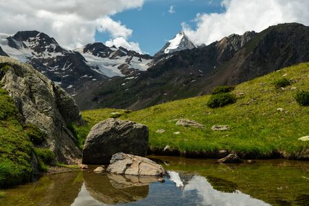 Martell valley in South Tyrol (Italy) on a partly cloudy day in summer, Koenigspitze, Gran Zebru reflecting in a small pond near Marteller Huette