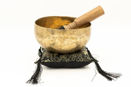 A singing bowl standing on a black cushion, white background