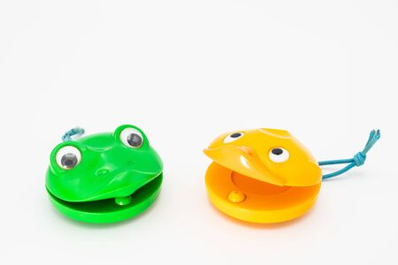 Closeup of two castanets for children in shape of a yellow duck and green frog