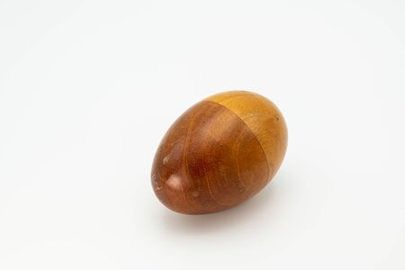 Closeup of a wooden egg shaker in front of a white background