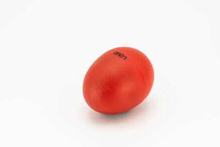 Closeup of a loud red egg shaker lying on a white underground
