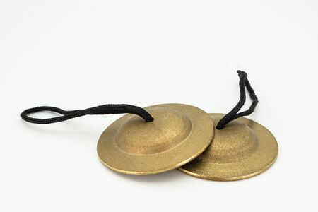 Closeup of a pair of finger cymbals lying on a white underground