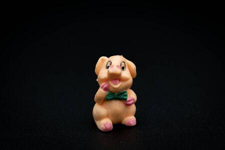 Closeup of a figurine of a small sitting piggy, black background Foto de archivo - 138468243