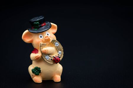 Figurine of a small piggy with a black hat and a horseshoe, black background Foto de archivo - 138471926