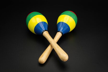 Closeup of a pair of colorful maracas lying on a black underground