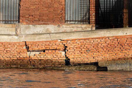 A broken brick wall in water in Murano on a sunny day in winter Banco de Imagens