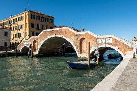 Canal with boats in Venice (Italy) in winter, bridge Ponte di Tre Archi