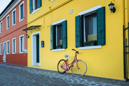 Bicycle in front of a yellow house in Burano (Venice, Italy) on a sunny day in winter