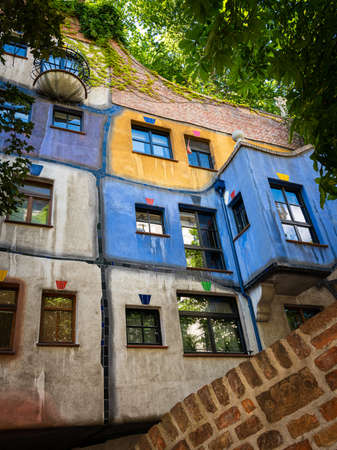 Vienna, Austria - June 25, 2020: The Hundertwasser Haus on a sunny day in summer. This house has become world-famous due to the lack of straight lines, the colourful paintings and the dense greenery.
