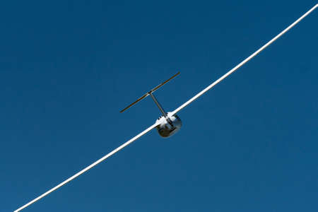 Mariazell, Austria - June 12, 2020: White sailplane from behind on a sunny day in summer, blue sky