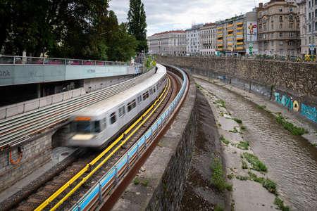 Vienna, Austria - June 18, 2020: Underground train near the river Wienfluss on a cloudy day in summer. This is the oldest underground line (U4) in Vienna