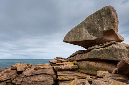 Interesting rock formation (Rock of the Dé) on Pink Granite Coast in northern Brittany (France), on a sunny day in summer Imagens