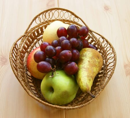 Basket with fresh fruit on wooden table photo