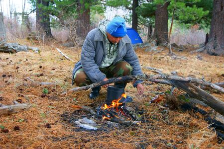 blazes: Man beside campfires in spring wood