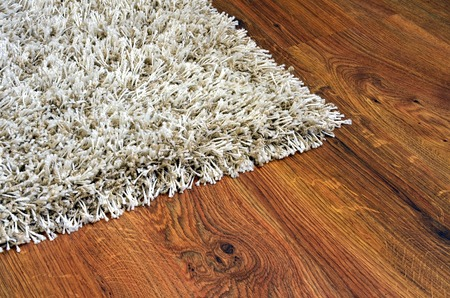 Parquet floor of the brown wooden planks and white shaggy carpet photo