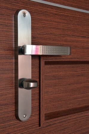 Modern chrome metallic door handle on wooden door photo
