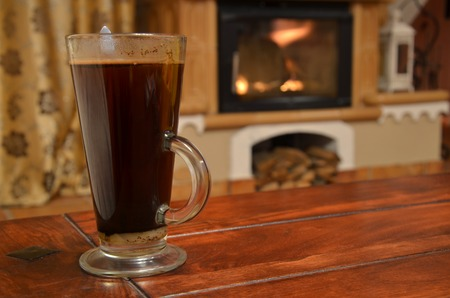 Cup of coffee on wooden table still life ahead of fireplace photo