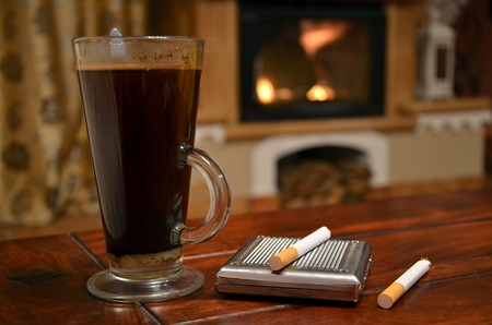 Cup of coffee, cigarette and snuffbox still life ahead of fireplace photo