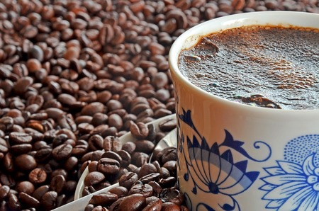 Detail of porcelain cup of coffee and saucer in pile of brown coffee beans photo