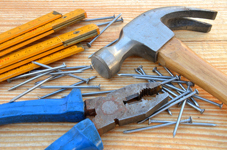 Claw hammer, carpenter meter, pliers and nails on wooden desk background photo