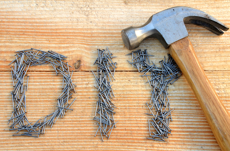 DIY (do it yourself) text from small nails and hammer on wooden desk background photo