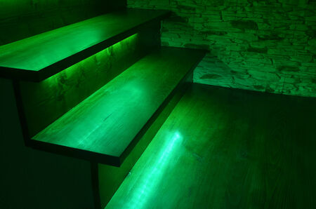 Green illuminated wooden stairs and rough stone wall photo