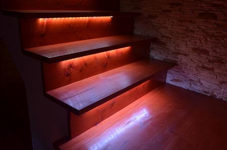 Blancos escaleras de madera iluminados y muro de piedra en bruto