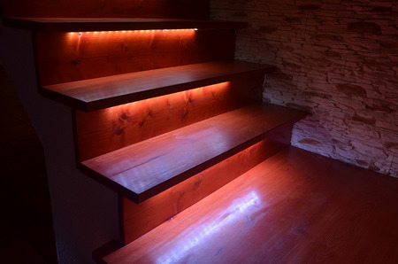 White illuminated wooden stairs and rough stone wall Imagens - 34619468