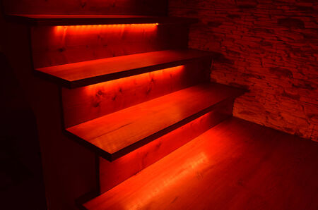 Red illuminated wooden stairs and rough stone wall photo