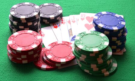 flush: Red, blue, green, white and black poker chips and royal flush on green table