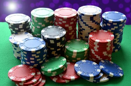 Red, blue, green, white and black poker chips pile on green table photo