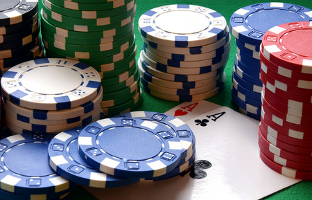 Red, blue, green, white and black poker chips pile and aces on green table photo