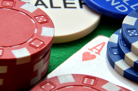 Blue, green and red poker chips pile and ace detail photo